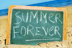 Summer forever. Written in a chalkboard on a beach royalty free stock images