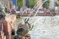 Summer fountain made of bronze geese. People are resting near the fountain. stock photo