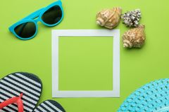 Summer frame. Paper frame for your text, flip flops, glasses and seashells on bright green background. top view royalty free stock photo
