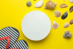 Summer frame. Paper frame for your text, flip flops and seashells on bright yellow background. top view royalty free stock images