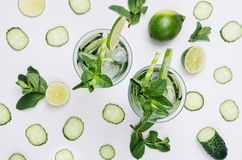 Summer fresh background - cold natural refreshing cocktail with slices cucumber, lime, mint, ice, straw on white wood plank. royalty free stock photos
