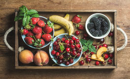 Summer fresh fruit and berry variety in rustic wooden tray. Over wooden backdrop, top view, horizontal composition Royalty Free Stock Photos