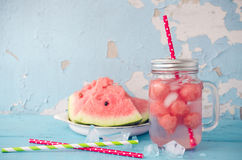 Summer fresh fruit flavored infused water of watermelon. Fresh fruit flavored infused detox water of watermelon. Summer drink in glass mason jar with ice on blue Royalty Free Stock Photos