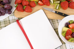 Summer fresh fruit salad bowl, chopping board, cookbook, copy space Stock Images