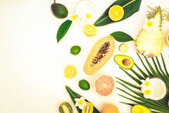 Summer fresh fruits. Fresh exotic cuted fruits with green tropical leves flat lay top view border, summer healthy diet background, toned stock images