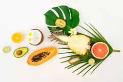 Summer fresh fruits. Fresh exotic cuted fruits slices with green levaes flat lay top view pattern, summer healthy diet background stock photos