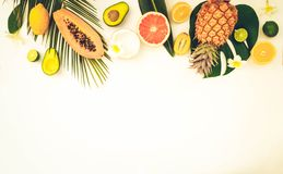 Summer fresh fruits. Fresh exotic fruits with green tropical leves flat lay top view border, summer healthy diet background with copy space, toned royalty free stock photo