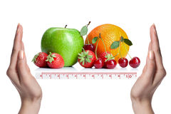 Summer fresh fruits with scale and hands Royalty Free Stock Images