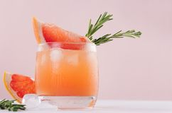 Summer fresh homemade grapefruit lemonade with ice cubes and rosemary closeup on light pink background. Summer fresh homemade grapefruit lemonade with ice cubes Stock Photo