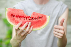 Summer and fresh watermelon theme: a man holds a slice of watermelon on a green background Stock Photos