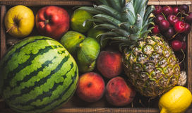 Summer friut variety on wooden background, top view. Watermelon, pineapple, lemon, figs, peach, sweet cherry and apple royalty free stock photo