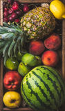 Summer friut variety in wooden tray over dark rustic background. Summer friut variety in wooden tray over wooden background, top view. Watermelon, pineapple royalty free stock photos