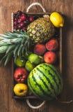 Summer friut variety in wooden tray over dark rustic background. Summer friut variety in wooden tray over wooden background, top view. Watermelon, pineapple stock photo