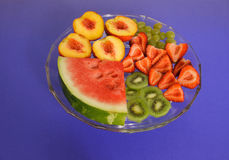 Summer Fruit. A delicious plate of summer fruit - kiwi, peaches, watermelon and strawberries Royalty Free Stock Photos