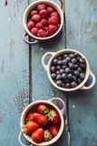 Berry fruits. Summer fruit background, top view of berries inside ceramic colored cocotte, blueberries, strawberries, raspberries, flat lay, blue table. Detox Stock Images