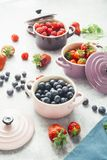 Berry fruits. Summer fruit background, top view of berries , smoothie ingredient, inside ceramic colored cocotte, blueberries, strawberries, raspberries, flat Royalty Free Stock Photography