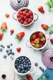 Berry fruits. Summer fruit background, top view of berries , smoothie ingredient, inside ceramic colored cocotte, blueberries, strawberries, raspberries, flat Royalty Free Stock Photos