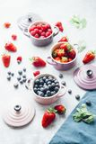 Berry fruits. Summer fruit background, top view of berries , smoothie ingredient, inside ceramic colored cocotte, blueberries, strawberries, raspberries, flat Stock Images