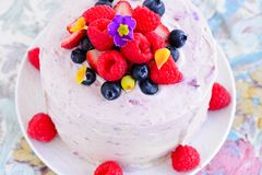 Eggless summer berry fruit cake. Summer fruit cake with edible flowers, whipped cream raspberries and blue berries stock photography
