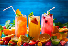 Summer fruit drinks. Different types of summer drinks in glasses, cubes of ice and slice of fruits  on blue table. Healthy vitamin fruit and berry drinks Stock Photography