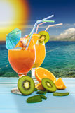 Summer fruit drinks. Or juice with ocean beach on background Royalty Free Stock Photography