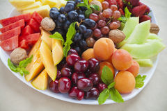 Summer fruit platter. Colorful summer fruit platter with pineapple, watermelon, cherries, apricots, strawberries, cantaloupe, walnuts and mint Stock Image