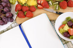 Summer fruit salad, bowl, cutting board, cookbook, copy space Royalty Free Stock Photos