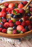 Summer fruit salad in wooden bowl closeup. vertical Stock Photo