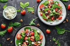 Summer Fruit Strawberry, spinach Salad with walnut, feta cheese balsamic vinegar, kale. in a plate. concepts health food royalty free stock images