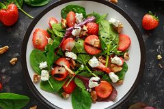 Summer Fruit Strawberry, spinach Salad with walnut, feta cheese balsamic vinegar, kale. in a plate. concepts health food Stock Photo