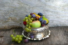 Summer fruit variety. Fruits in silver pot on vintage background Stock Photos