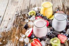 Summer fruits and berries smoothie. Drink. Vitamin diet snack beverage, with blueberries, strawberries, blackberries, kiwi. Dark blue concrete background copy stock photography