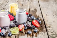 Summer fruits and berries smoothie. Drink. Vitamin diet snack beverage, with blueberries, strawberries, blackberries, kiwi. Dark blue concrete background copy stock photos