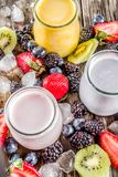 Summer fruits and berries smoothie. Drink. Vitamin diet snack beverage, with blueberries, strawberries, blackberries, kiwi. Dark blue concrete background copy stock photo