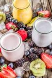 Summer fruits and berries smoothie. Drink. Vitamin diet snack beverage, with blueberries, strawberries, blackberries, kiwi. Dark blue concrete background copy stock image
