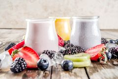 Summer fruits and berries smoothie. Drink. Vitamin diet snack beverage, with blueberries, strawberries, blackberries, kiwi. Dark blue concrete background copy royalty free stock photography