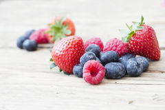 Summer fruits and berries, strawberries, blueberries, raspberrie. Natural shot on old wooden background of organic seasonal summer berries Royalty Free Stock Image