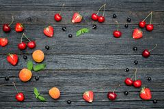Summer fruits on a black wooden background. Place for text.  Royalty Free Stock Image