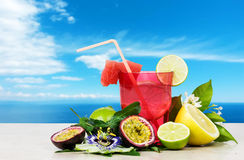 Summer fruits cocktail against relaxing sky background Stock Photo