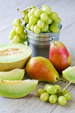 Summer fruits. Grapes, melon and pears, wooden background Royalty Free Stock Images