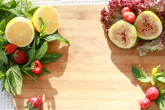 Summer fruits. Lemon, fig, strawberry on wooden table Royalty Free Stock Photography