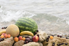 Summer fruits on the rocks against the blue sea. Royalty Free Stock Images