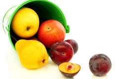 Summer fruits spilling from green bucket. Royalty Free Stock Photo
