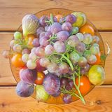 Summer fruits on a table against a wooden table Stock Photos