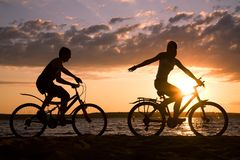 Summer fun. Silhouettes of happy couple riding their bicycles on seashore at sunset