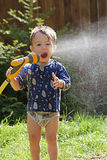 Summer fun. A little boy spraying a hose, summer scenic Stock Images