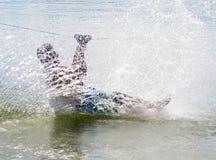 Summer Fun. A Man rides a zip line into a lake creating a big splash Stock Photos