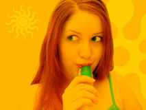 Summer Fun. Summer themed design. Woman in orange tones eating green freeze pop. Summer themed icons stock photo