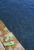 Summer fun. Overhead view of flipflop sandals on pier beside lake Stock Photos