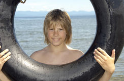 Summer Fun. Boy holding a tube at the beach Royalty Free Stock Photography